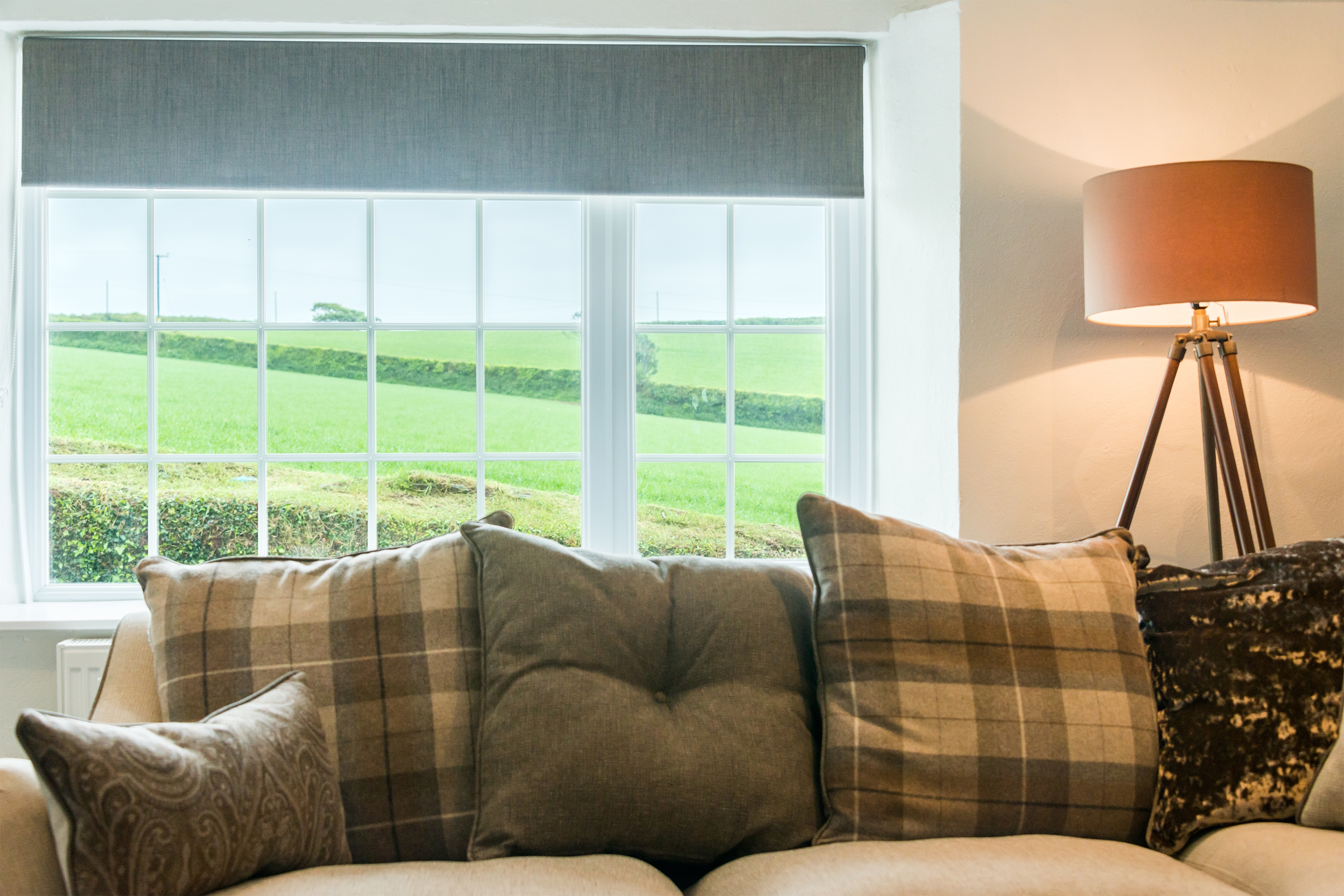 Tweed cushions on sofa in front of window overlooking fields.