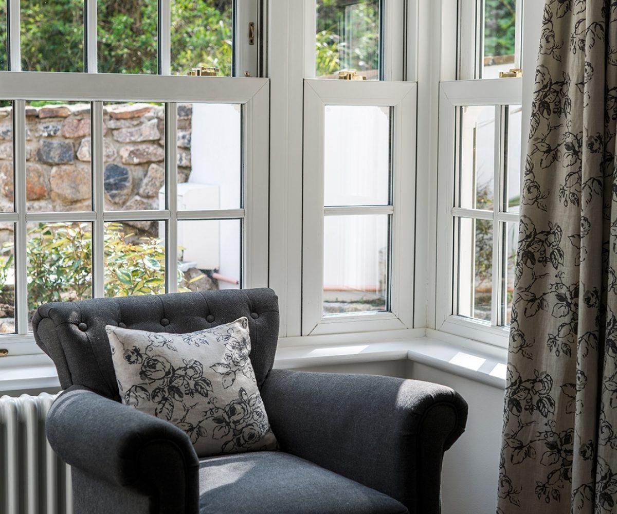 Dark armchair in corner with windows behind.