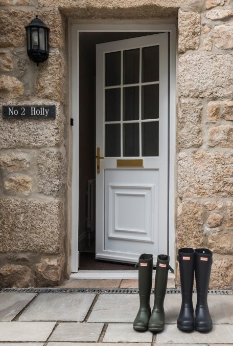 Front door of house with wellies on clean patio.