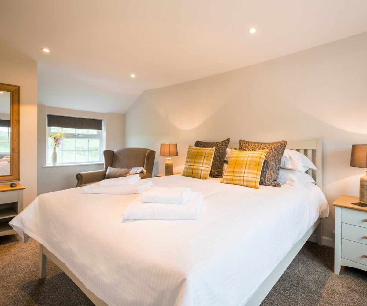 Large bed in warmly lit room.