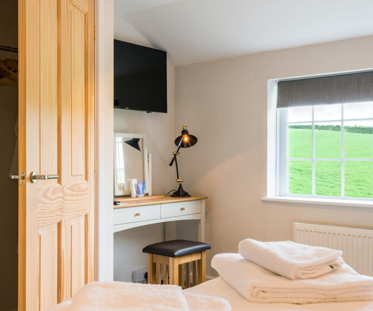 Small room with desk and view of fields.