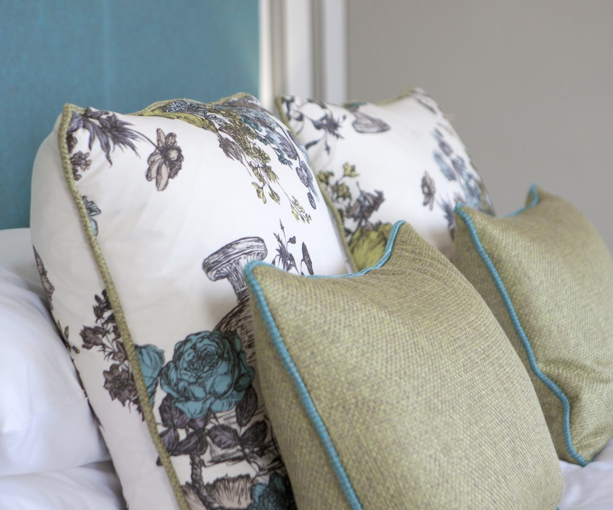 Green and patterned cushions on bed with blue headboard.