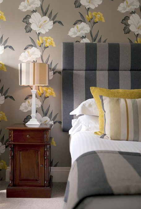 Bed with striped headboard against bold floral wallpaper.