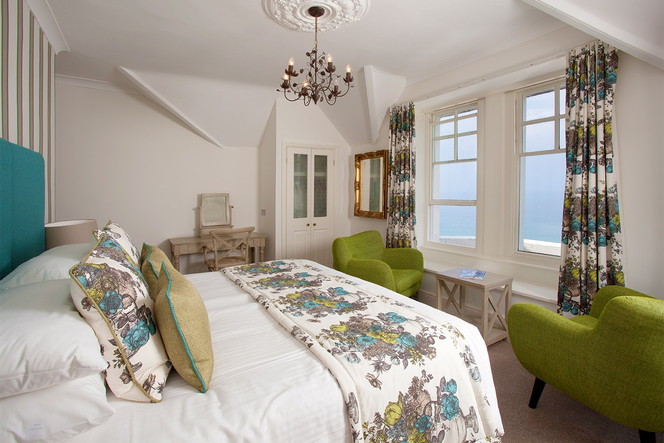 Double bedroom with low ceilings and floral bedpsread.