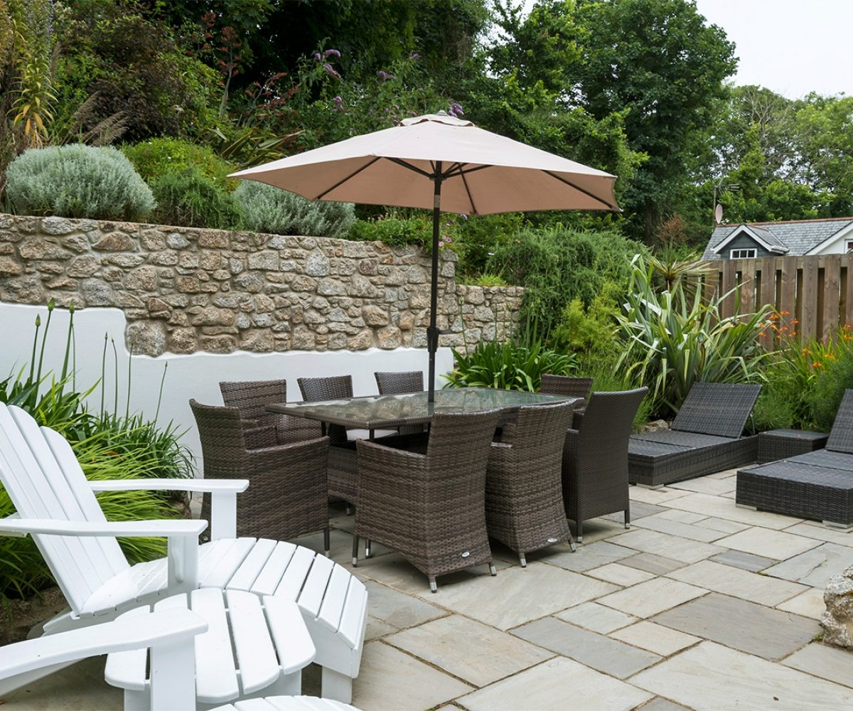 Patio area with garden furniture and stone wall behind.