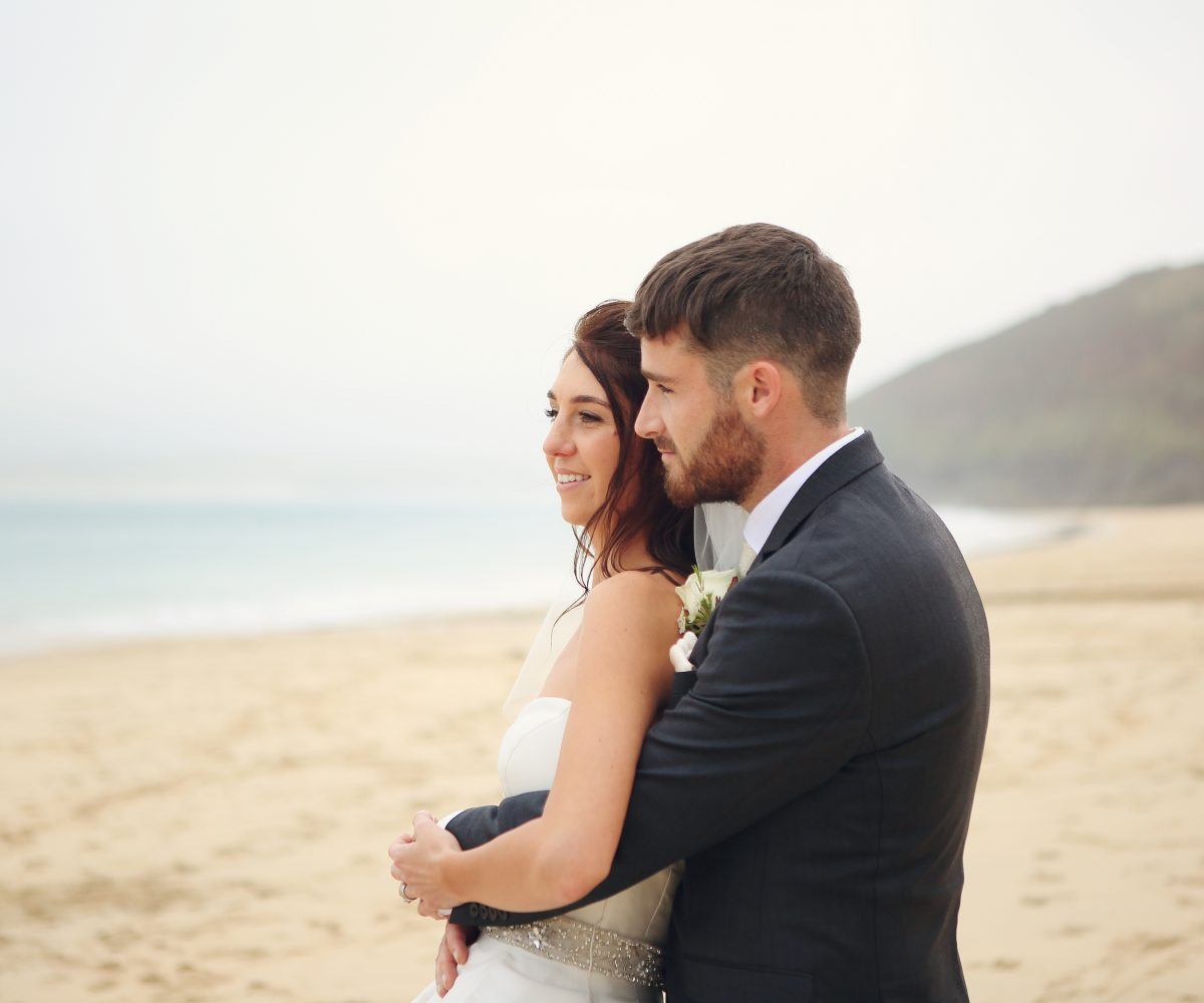 Newlyweds cuddling on Carbis Bay Beach.