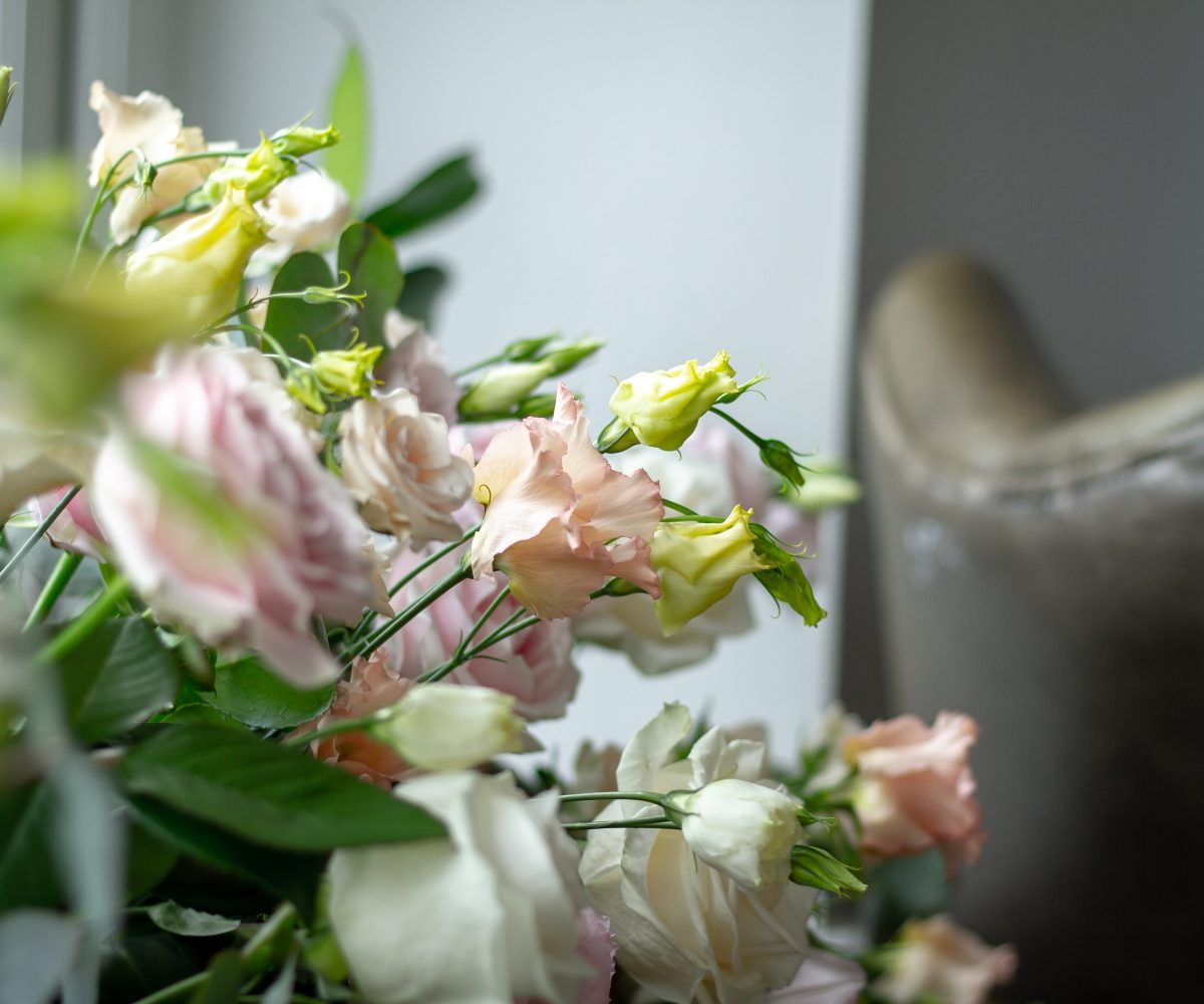 Wedding flowers with armchair in background.
