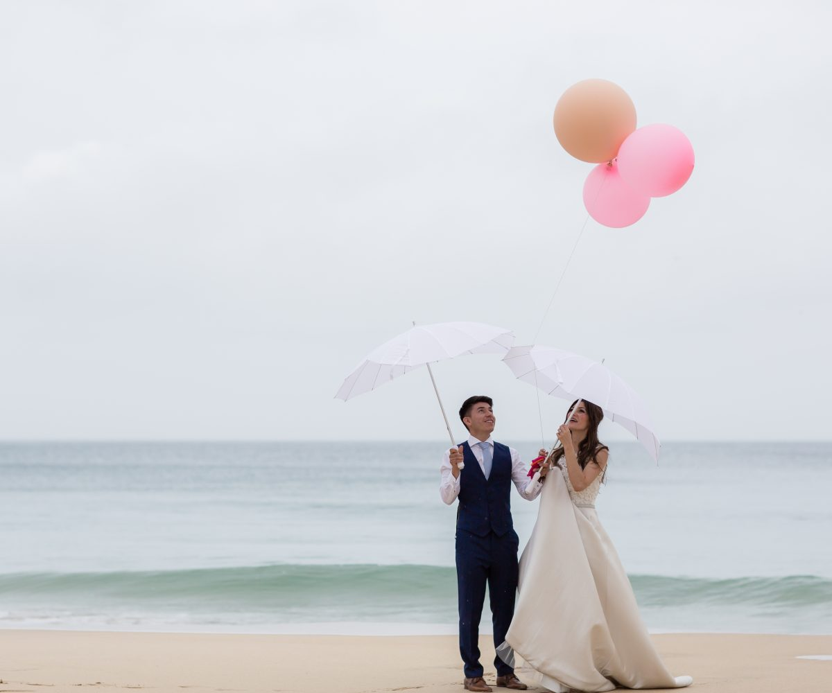 Bride and groom with pink balloons on Carbis Bay beach.