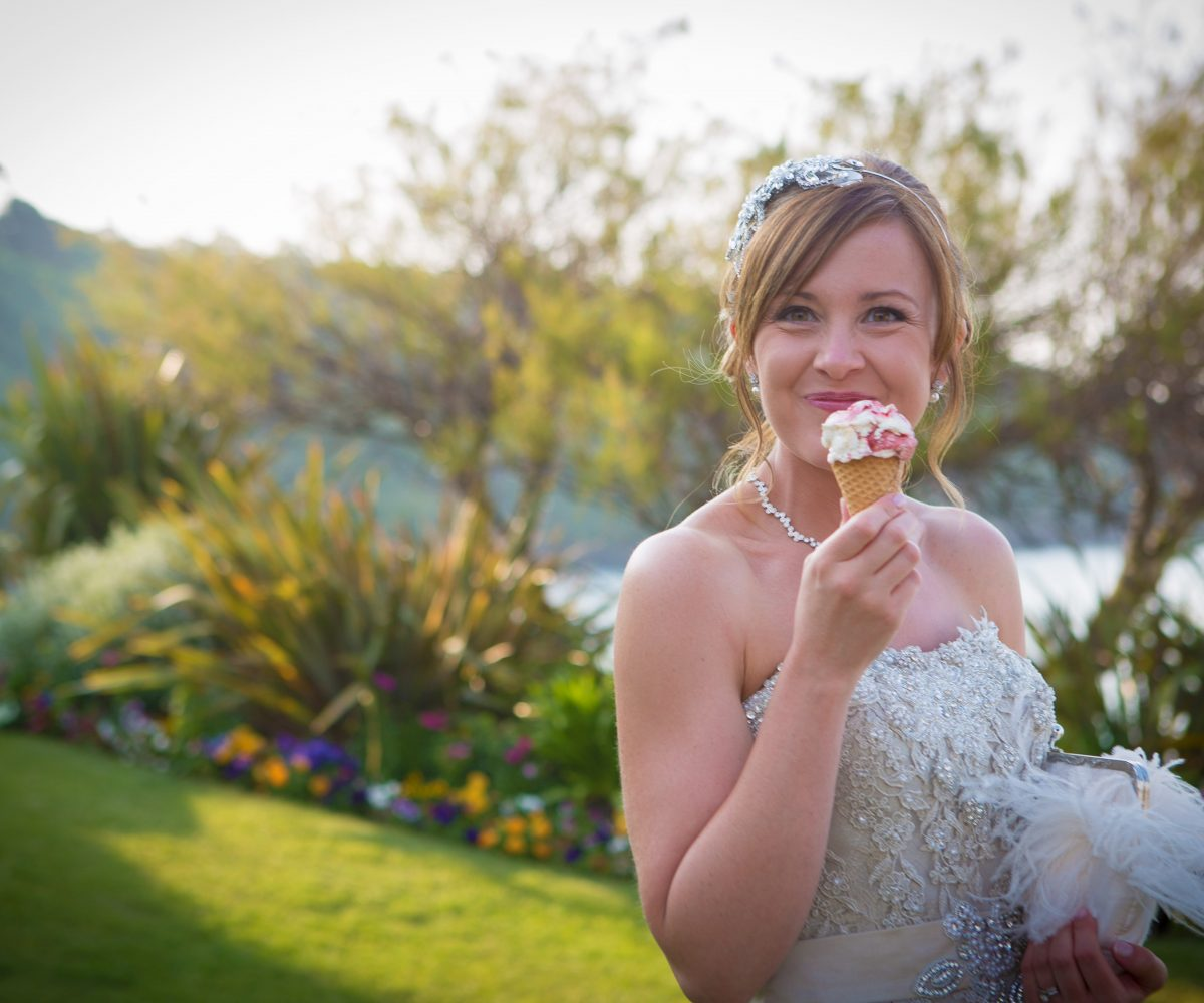 Bride enjoying ice cream cone with lawn behind.