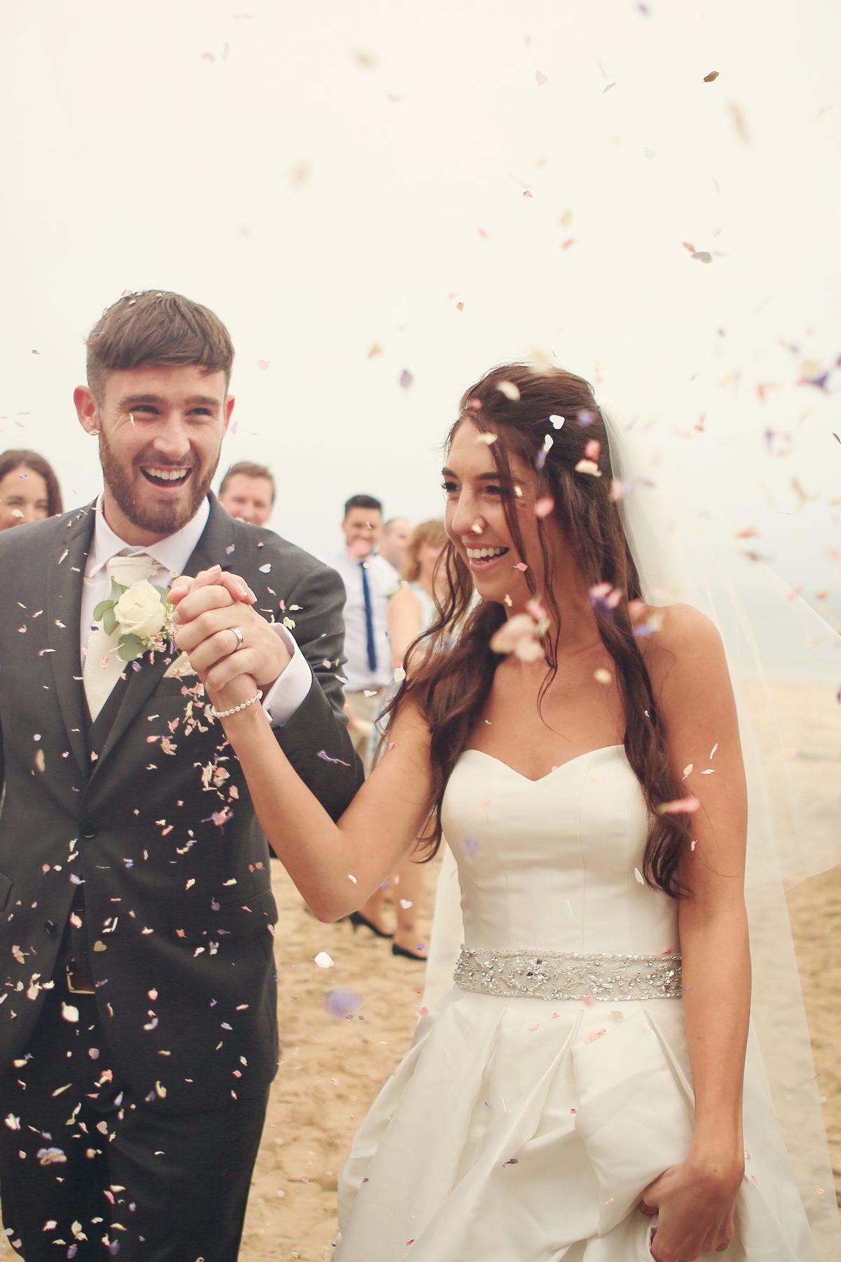Confetti on bride and groom on beach.