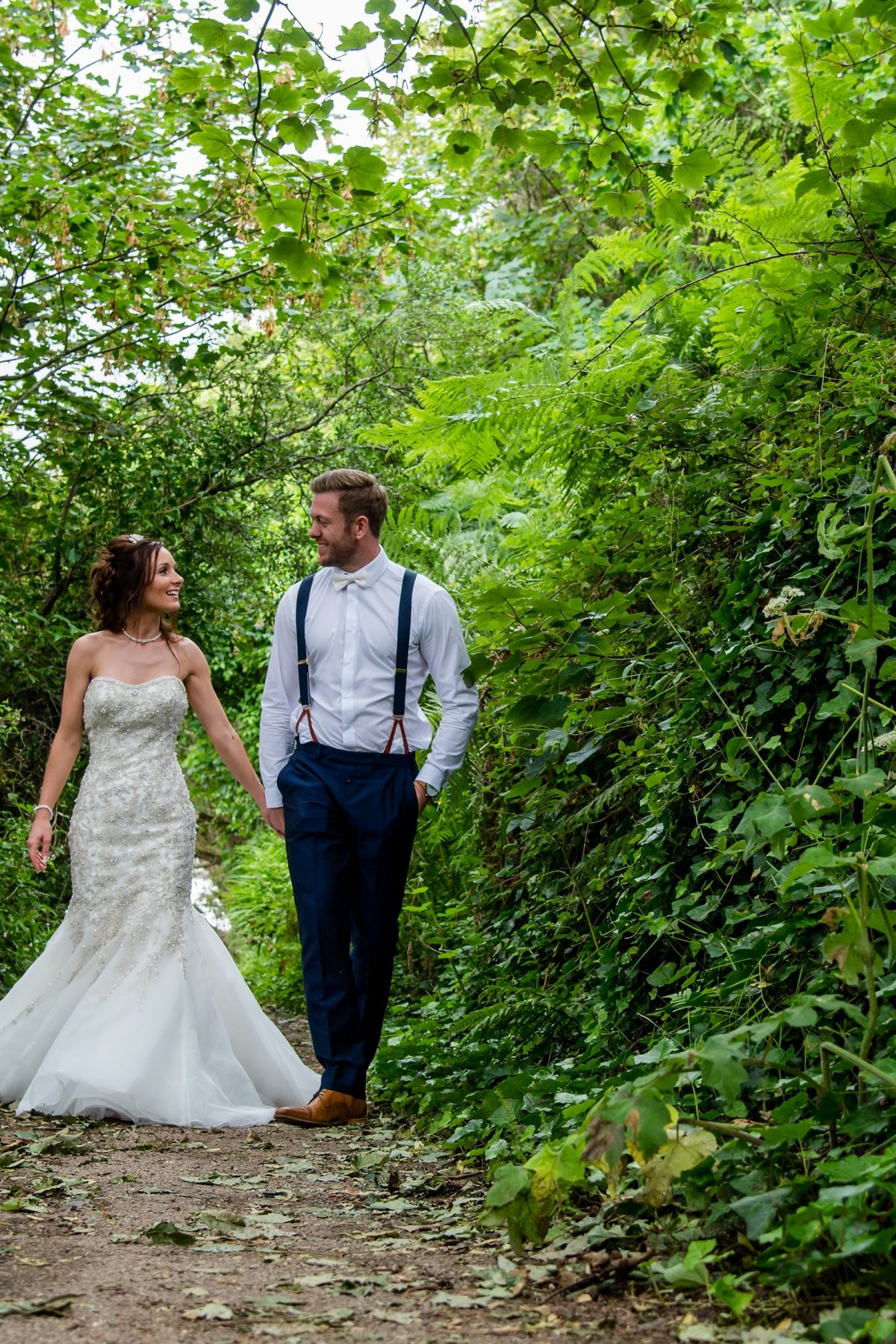 Bride and groom walking in woodland.