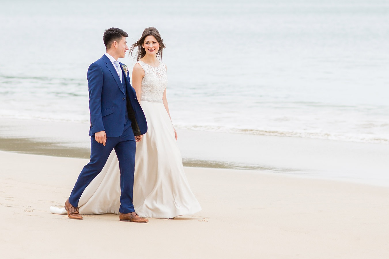 Bride and groom walking along Carbis Bay beach.